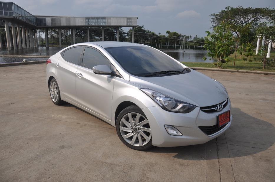 """รถยนต์ที่ได้รับรางวัลรถยนต์ยอดเยี่ยมแห่งปี 2556 แห่งอเมริกาตอนเหนือ (2012 North America Car of the Year) กับสุดยอดยนตรกรรมอันยอดเยี่ยมจากเกาหลีใต้ คันนี้กับรถยนต์ All New Hyundai Elantra รถ Compact แนวหรู look premium คันนี้ ซึ่งจัดเป็น Generation ที่ 5 เข้าไปแล้ว โดยในรุ่นแรกๆ ที่เปิดตัวเมื่อราวเกือบ 20 ปีก่อนนั้นถือเป็นรถยนต์ที่เน้นทำราคาถูกเลยก็ว่า กับภาพลักษณ์ของ Hyundai ในสมัยนั้นที่ถูกตีตราว่าเป็นรถยนต์ราคาประหยัด แต่กลับมาคราวนี้ กลับจากหลังมือเป็นหน้ามือกันเลย โดยการเปิดตัวออกแนวพรีเมียม เรียบหรู และราคาเปิดตัวที่โหดกว่ารถยนต์ญี่ปุ่น เครื่อง 2.0 บ้านเราอีกหลายๆรุ่น การกลับมาคราวนี้ Elantra จะเป็นหนึ่งในแม่ทัพของ Hyundai ที่จะช่วยสร้างแบรนด์ให้กับ Hyundai กลับมาอีกครั้งกับ ในคราบรถหรู ที่จะไม่ใช่รถยนต์เกรดต่ำราคาถูกอีกต่อไป Let """"Put Your Sense on FIRE """" Together"""